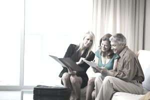 Businesswoman talking to couple on sofa
