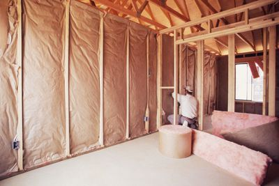 Installing insulation into wall of new home