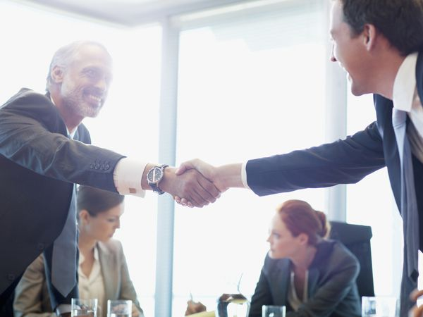 two businessmen shaking hands, two businesswomen sitting in the background