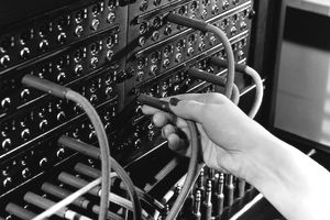 Old Switchboard with woman's hand plugging in wire for an outgoing call
