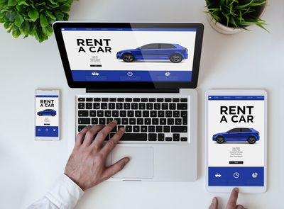 office tabletop with tablet, smartphone and laptop showing rent a car website