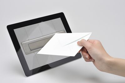 Person holding an envelope in front of a tablet showing a mail slot