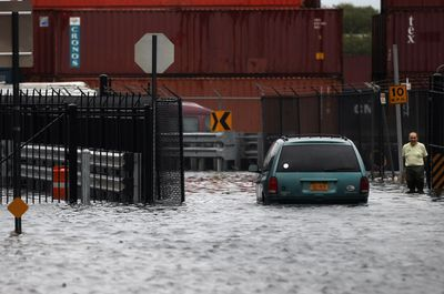 A person walks through a flooded street after Hurricane Irene on August 28, 2011 in the Red Hook neighborhood of the Brooklyn borough of New York City.