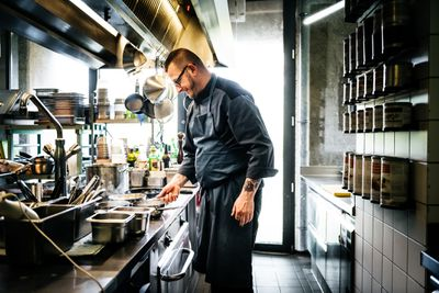 Head Chef Cooking On Hob In Well Stocked Restaurant Kitchen