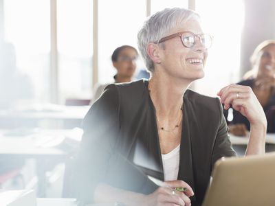 An older businesswoman smiles from her seat at a classroom desk.