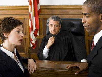Counterparties in a business dispute talk in front of a judge sitting at the bench