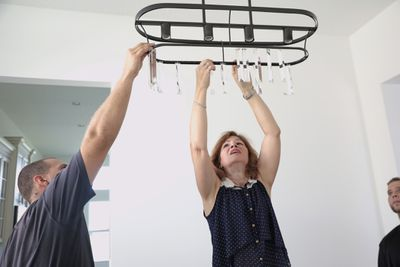 A woman landlord and her associates hang a chandelier in the dining room of a clean, well-lit rental apartment.
