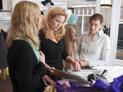 Group of women thoughtfully looking at a binder together, tracking their marketing results.