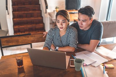 Couple using QuickBooks to manage finances on a laptop