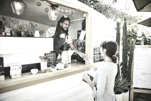 Barista at food truck accepting credit card payment from a customer
