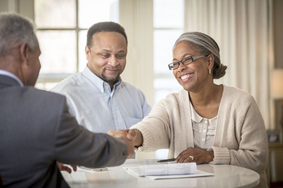 A couple meeting with a financial advisor and smiling