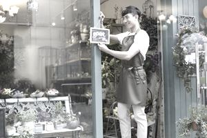 Florist holding an open sign.