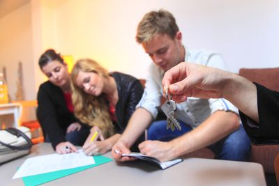 Home buyers writing a check with an agent holding a key.