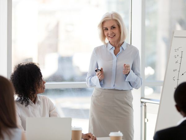 Middle-Aged Woman with Blond Hair Leading Office Meeting with Chart Behind Her.