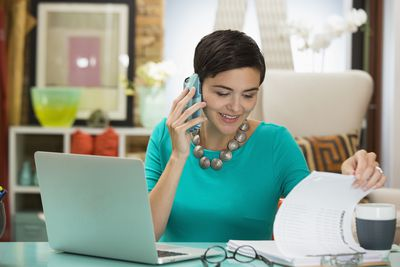 Businesswoman talking on phone with distributor