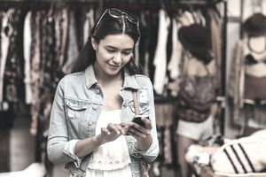 Young woman using a phone in a boutique