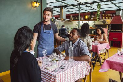 Male chef taking order from couple at table in restaurant