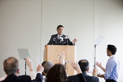 Businessman at podium giving press conference