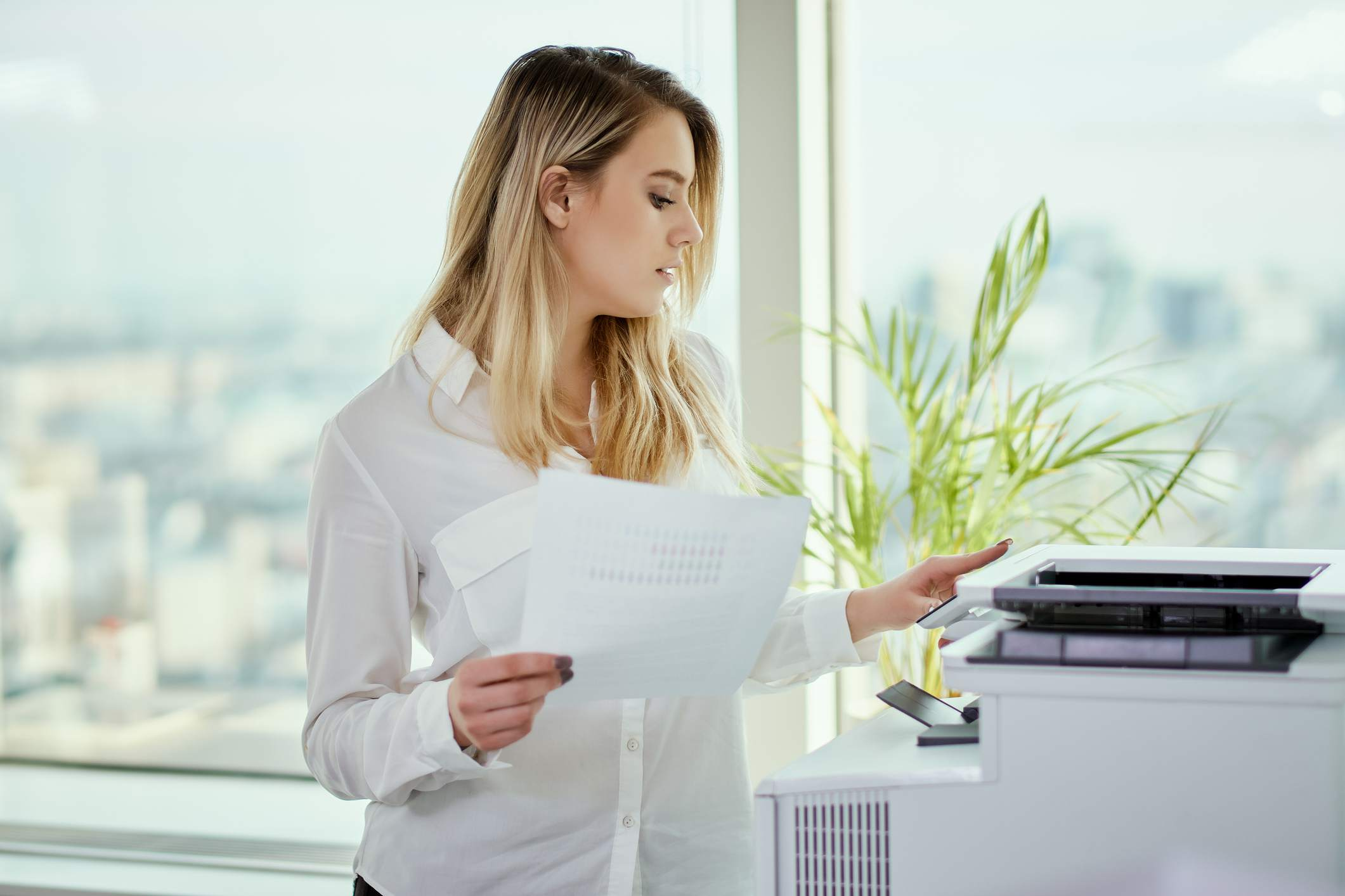 Businesswoman Holding Documents Using Printer At Office