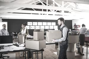 Room filled with office workers packing cardboard boxes while moving from one business address to another.