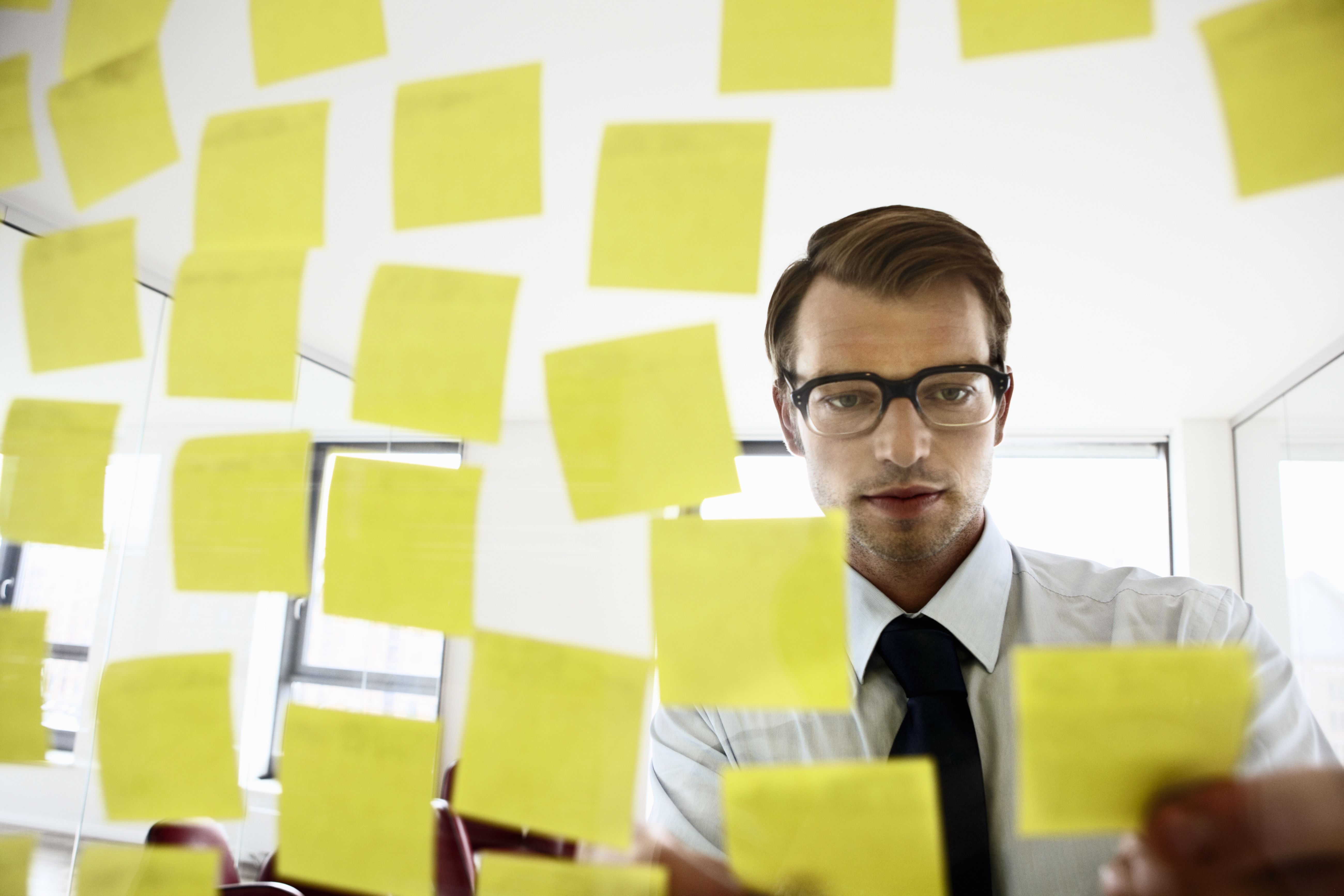 A man placing sticky notes on a mirror