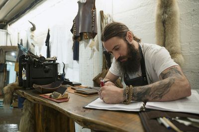 Shop owner sitting in his workshop at a table with various tools scattered about and working on his annual master budget held in a 3-ring notebook.