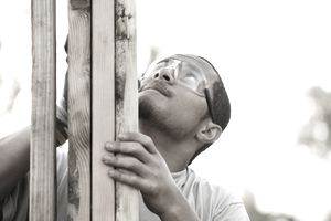Pacific Islander construction worker adjusting house frame