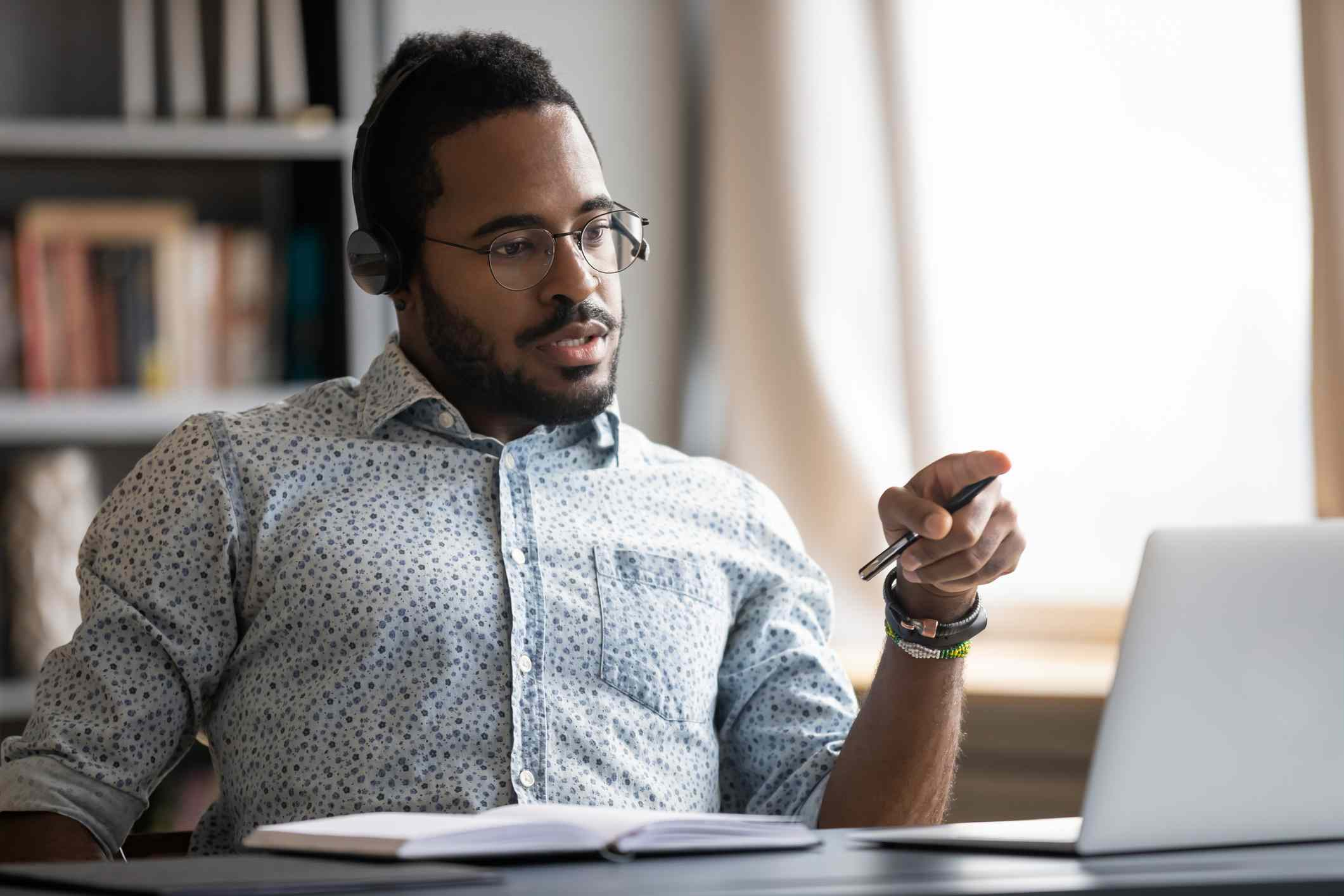 Focused biracial man in headphones busy working at workplace