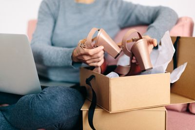 Woman packing a pair of shoes into box to be shipped out