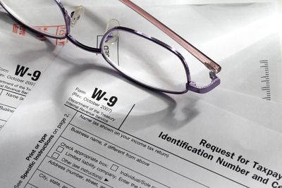 a blank Form W-9 with a pair of glasses laying on a desk