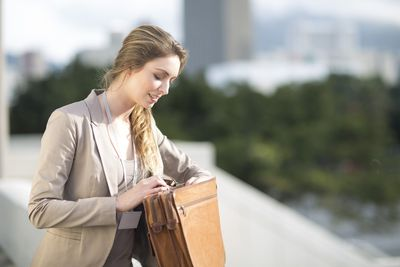 Businesswoman looking for something at her briefcase