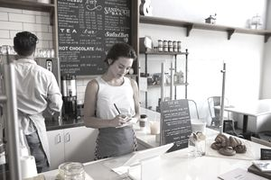 Couple working behind the counter at a coffee shop