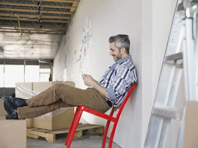 New business owner looking at his phone as he sits amongst boxes in his new store