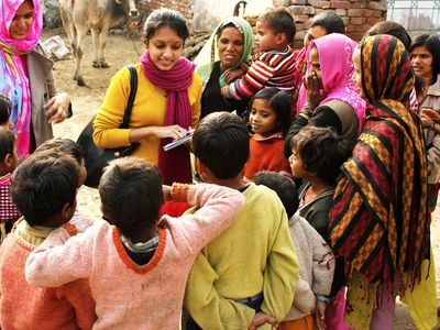 Two female social workers are interacting with a group of villagers comprising of children and female adults.