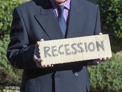 Closeup of a man in a suit holding a piece of cardboard that says