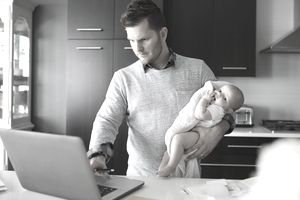 Father holding baby daughter and working at laptop in kitchen