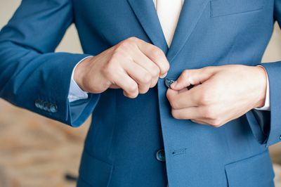 Close up of man buttoning blue suit