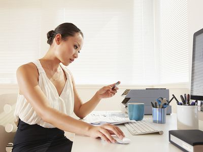 Woman on a computer at a desk, looking at her credit card