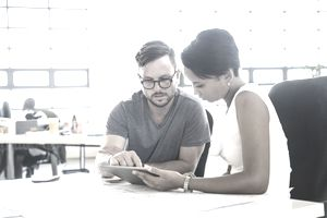 Man and woman in an office discussing a business plan on a tablet