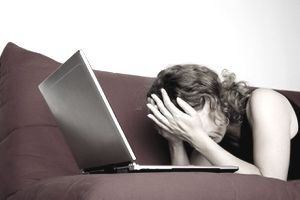 Frustrated woman lying on sofa with a laptop and her head in her hands