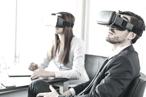 Two young business persons with virtual reality headsets in the office.