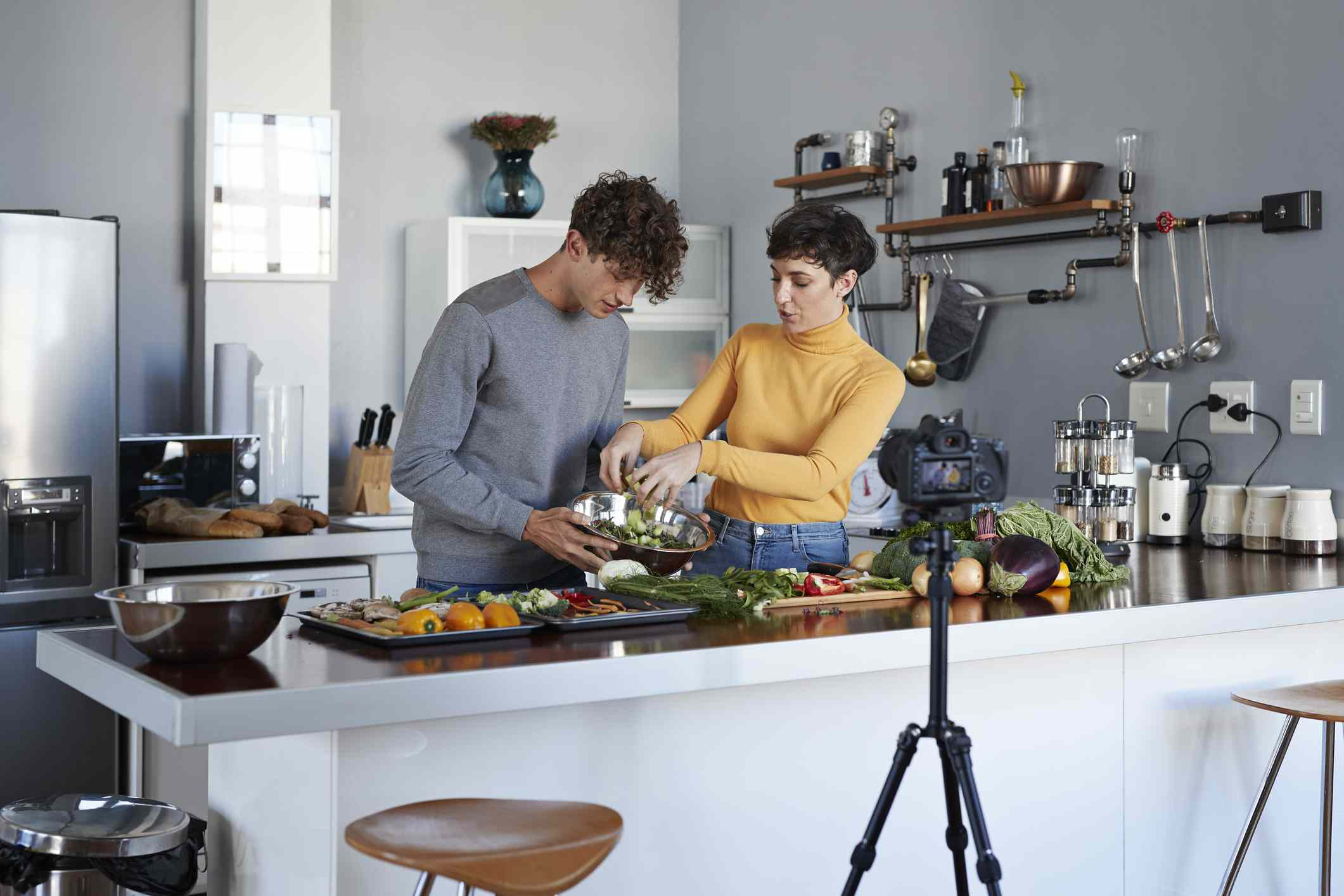 Two food vloggers making video while prepping vegetables in kitchen
