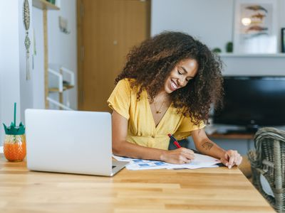 Young woman writing and on laptop, working at home