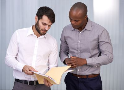 Two male business people discussing documents