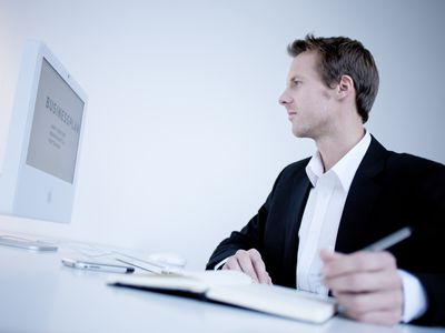 Young Businessman Looking at Business Plan on his Computer