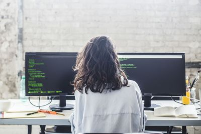 Rear view of female computer hacker coding at desk in creative office