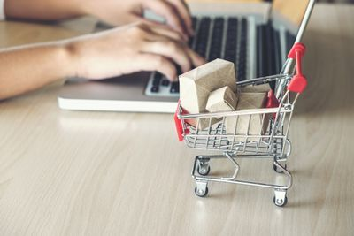 Close-Up Of Miniature Shopping Cart With Boxes By Person Using Laptop