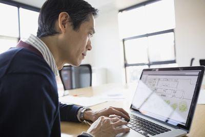 Man using laptop to manage his investment property.