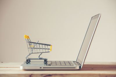 Small Shopping Cart On Laptop With Copyspace : Online Shopping Concept. E-commerce.