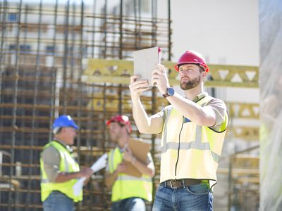 Construction Worker on a worksite filing a report with iPad